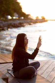 Zijwaartse vrouw die een foto van de zee neemt
