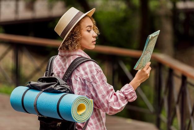 Zijwaartse vrouw die een kaart voor een nieuwe bestemming controleert