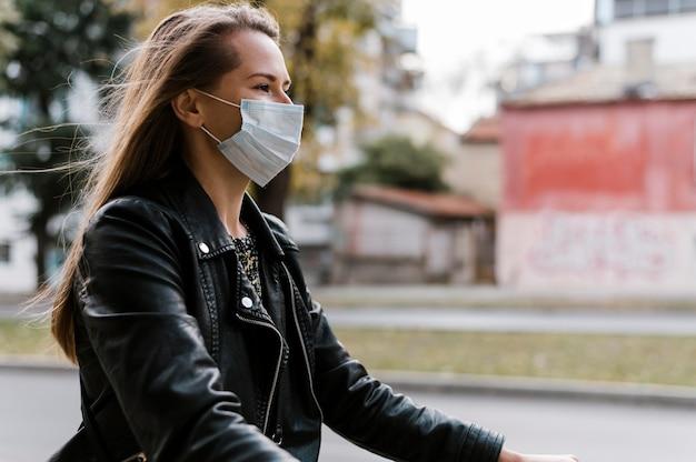 Zijwaartse vrouw die masker draagt en de fiets berijdt