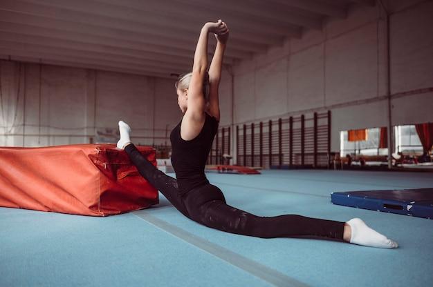 Zijwaartse vrouw die voor gymnastiekolympische spelen uitoefent