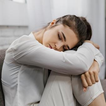 Zijwaartse vrouw kijkt verdrietig terwijl ze vanuit huis werkt