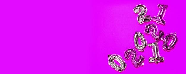 Zilver en goud folie lucht helium ballonnen op paarse achtergrond. veel nummers, bovenaanzicht, plat lag
