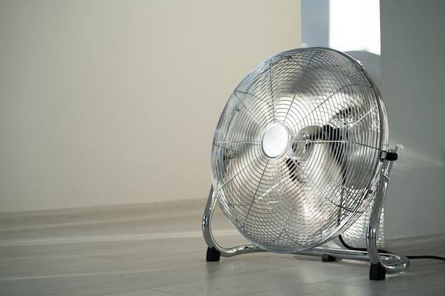 Zilver metalen ventilator op houten vloer thuis. kopieer ruimte