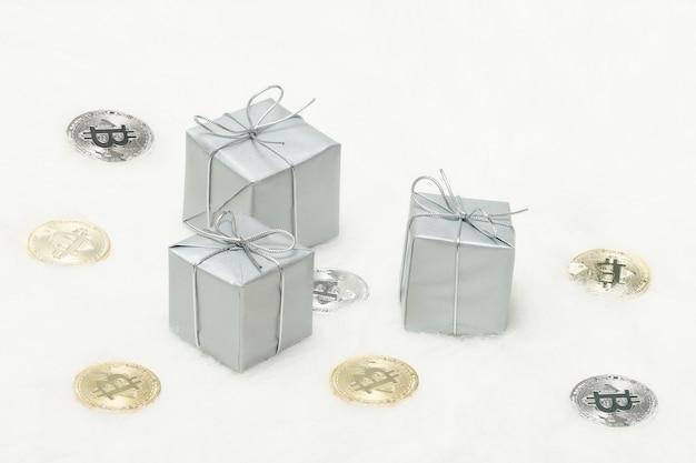 Zilverachtige geschenkdozen en bitcoins munten op een witte achtergrond