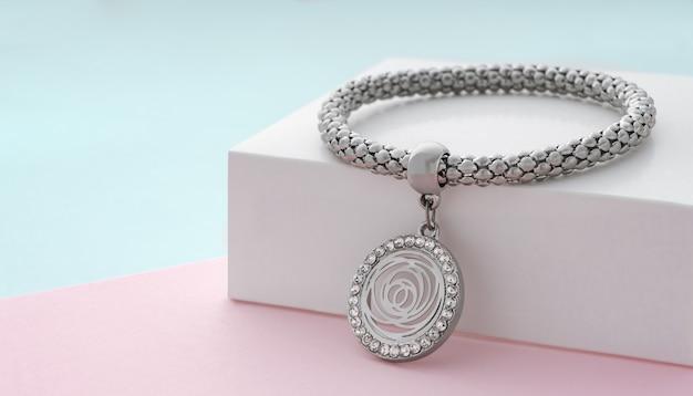 Zilveren armband met hanger in de vorm van een bloem op pastelkleurenachtergrond met kopieerruimte