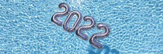 Zilveren ballonnen drijvend in blauwe water close-up achtergrond