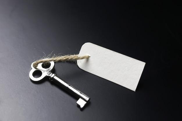 Zilveren bel en de sleutel bij de receptie in het hotel op een zwarte achtergrond