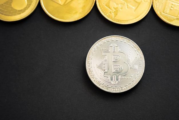 Zilveren bitcoin crypto-valutamunt naast anderen litecoin, ripple, monerd, ethereum-munt op zwart oppervlak.