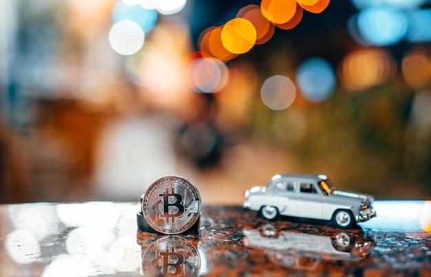 Zilveren bitcoin en moskvich 401 op tafel, gloeiend