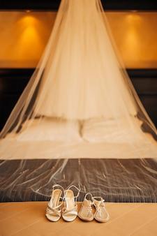 Zilveren bruidsschoenen op een bed vóór de ceremonie. bruiloft concept