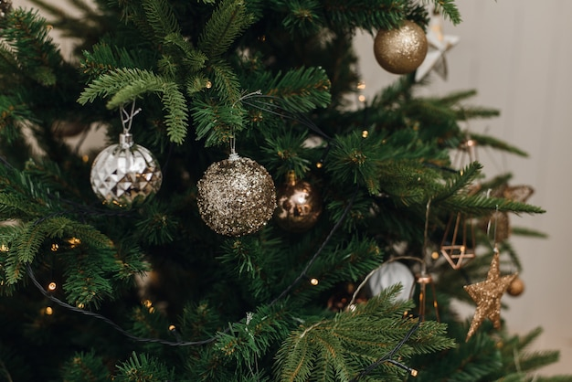 Zilveren, bruine gouden ornamentenballen op kerstmis kunstmatige boom binnenshuis