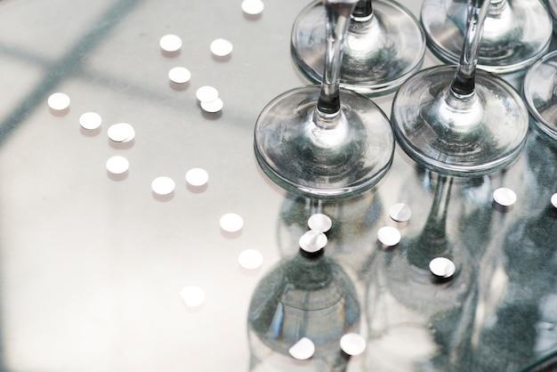 Zilveren confetti en reflectie van wijnglazen op tafel