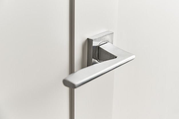 Zilveren deurklink op witte deur. meubelaccessoires, interieurelement