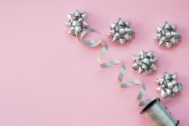 Zilveren en blauwe boog, lint op roze achtergrond.
