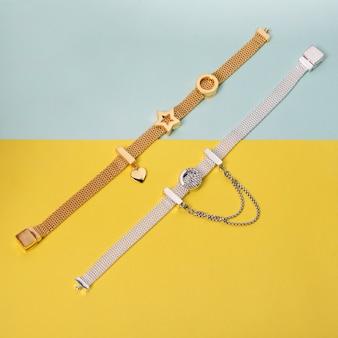 Zilveren en gouden armbanden op gele en blauwe achtergrond