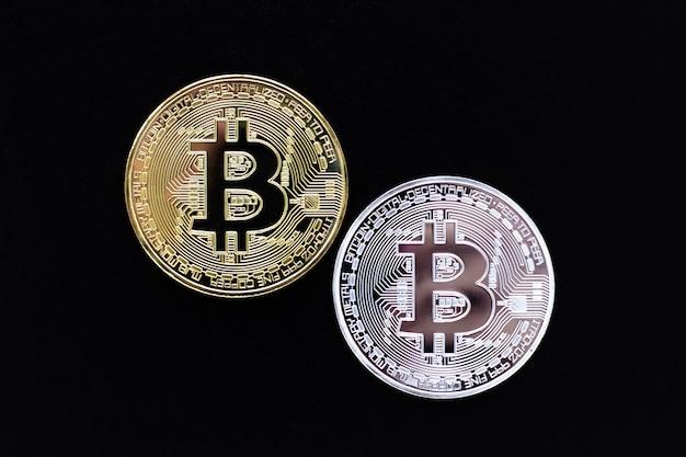 Zilveren en gouden bitcoins op zwarte achtergrond.