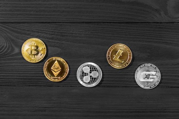 Zilveren en gouden munten met bitcoin, rimpel en etherische symbool op hout.