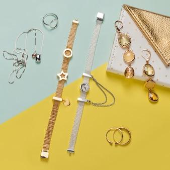 Zilveren en gouden sieraden op minimale gele en blauwe achtergrond