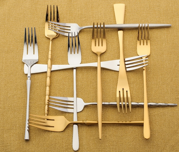 Zilveren en gouden vorken op een geel tafelkleed. creatief. abstract beeld van zilverwerk