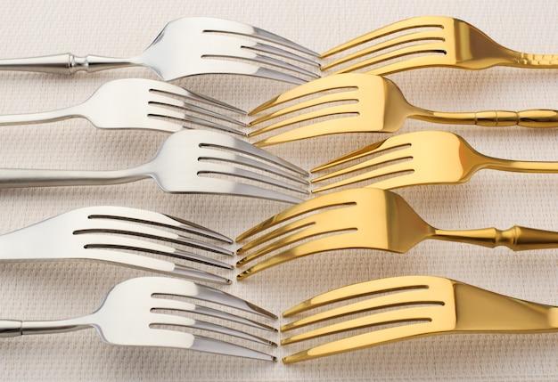 Zilveren en gouden vorken op een lichte achtergrond. bestek, keukengerei