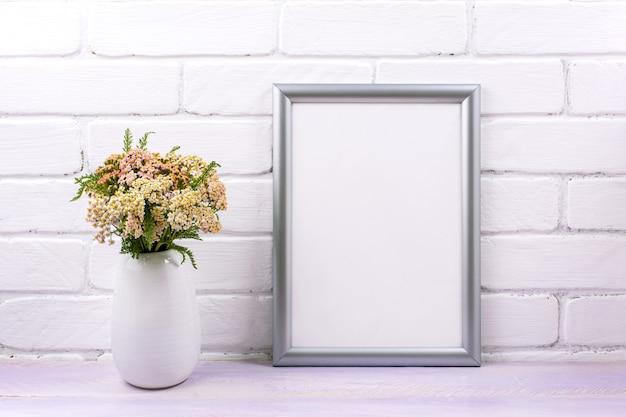 Zilveren frame mockup met roze duizendblad wilde bloemen in de vaas