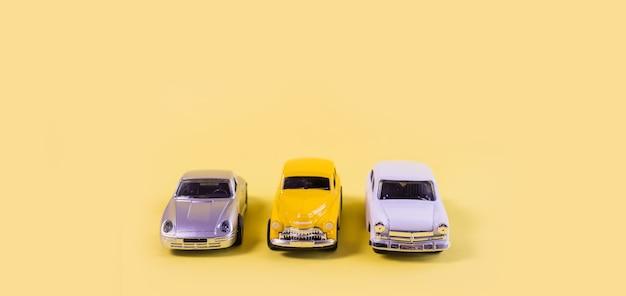 Zilveren, gele en witte speelgoedauto's geïsoleerd op gele achtergrond
