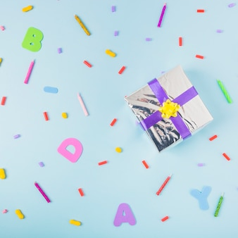 Zilveren geschenkdoos met paars en geel lint op rommelige blauwe achtergrond