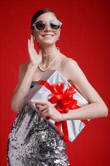 Zilveren geschenkdoos rode strik elegante vrouw in sequin jurk zonnebril accessoires op rode achtergrond