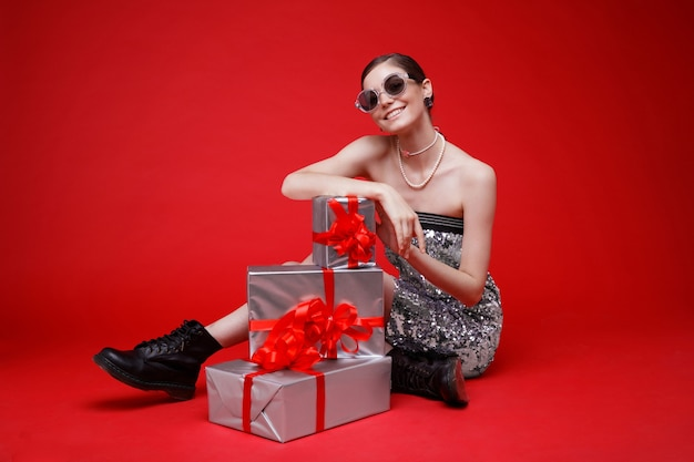 Zilveren geschenkdozen rode strikken vrouw in pailletten jurk zonnebril laarzen accessoires rode achtergrond