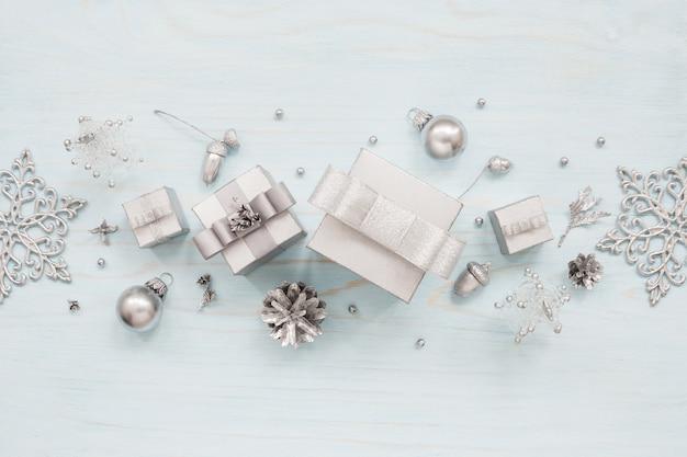 Zilveren geschenkdozen, sneeuwvlokken en kerstversiering op lichtblauwe tafel