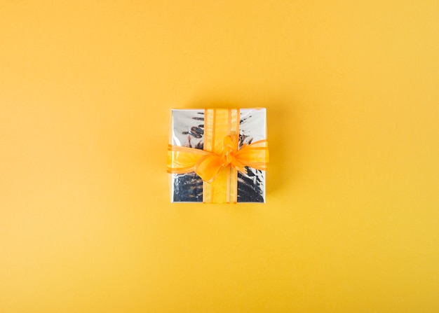 Zilveren giftdoos die met lint op gele achtergrond wordt verfraaid