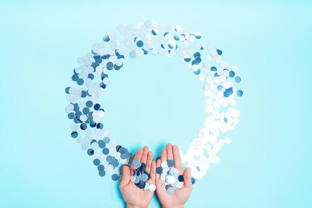 Zilveren glanzende confetti in de vorm van een rond kader op een blauwe achtergrond met een kopie van de ruimte.