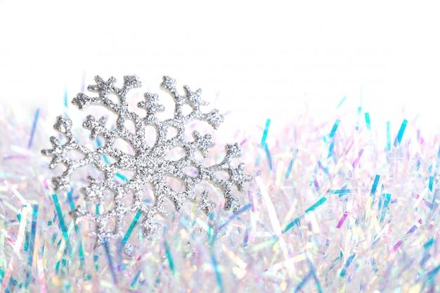 Zilveren glanzende sneeuwvlok op blauw en wit klatergoud op een witte achtergrond.