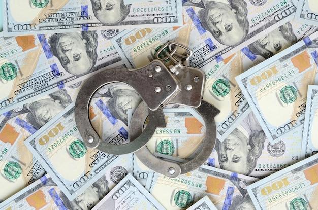 Zilveren handcuffs van de politie ligt op vele dollarrekeningen