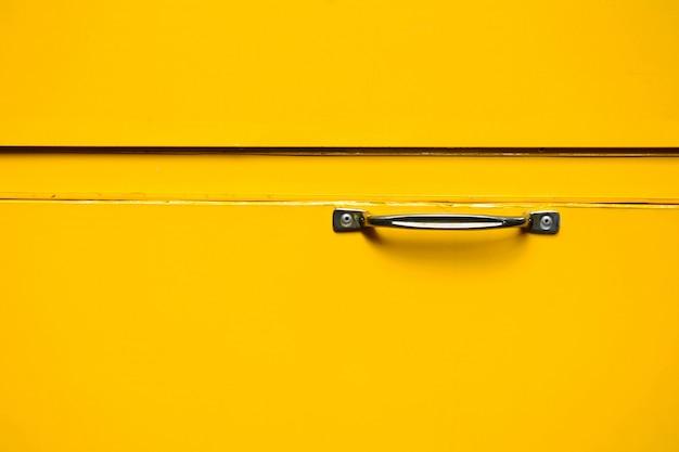 Zilveren handvat bij gele metalen doos