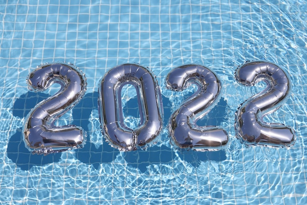 Zilveren heliumballonnen met getallen die in de achtergrond van de zwembadclose-up drijven