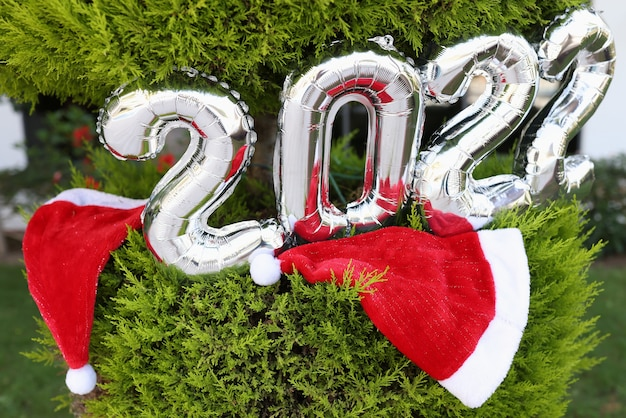 Zilveren heliumballonnen met nummers die aan de kerstboom hangen in de buurt van rode hoeden in de close-up van de kerstman...