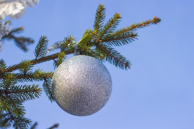 Zilveren kerstbal opknoping op een tak van een kerstboom