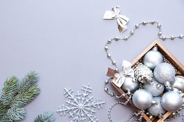 Zilveren kerstballen, kralen in een houten doos en dennentakken op een grijze achtergrond.