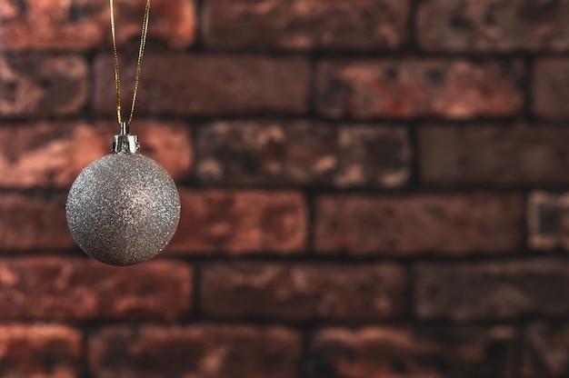 Zilveren kerstmisbal op de achtergrond van rode bakstenen muur