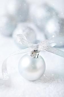 Zilveren kerstmisspeelgoed op een lichte achtergrond.