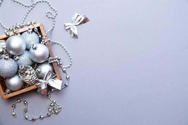 Zilveren kerstversiering in een houten doos op een grijze achtergrond.