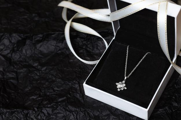 Zilveren ketting in geschenkverpakking op zwart.