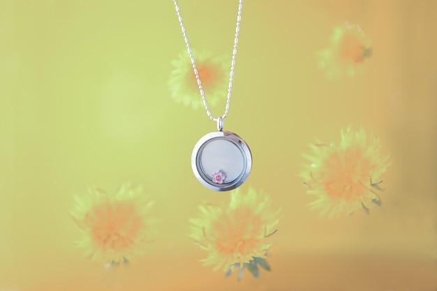 Zilveren ketting voor haar schijnt op gele achtergrond met paardebloemen. luxe zilveren sieraden kettingen met glas en kristallen. klein mooi edelmetaal cadeau voor vrouw. luxe uitingen
