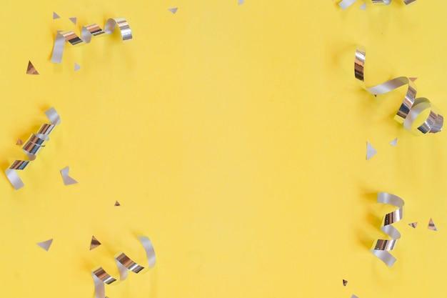 Zilveren kleur van rollend lint en confetti op gele achtergrond