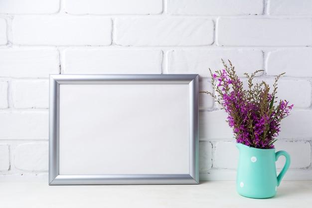 Zilveren landschapskader met kastanjebruine paarse bloemen in muntkan