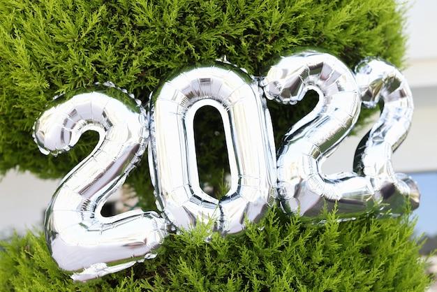 Zilveren lucht helium ballonnen met nummers opknoping op groene kerstboom close-up achtergrond