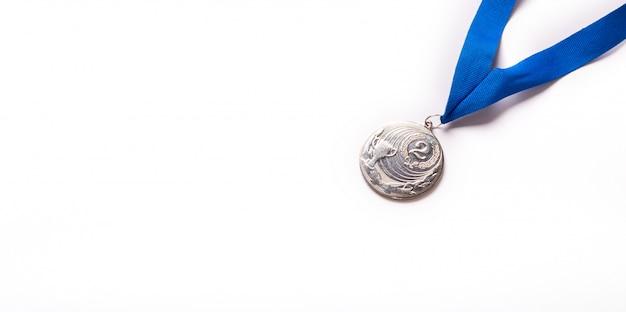 Zilveren medaille met blauw lint op witte achtergrond.