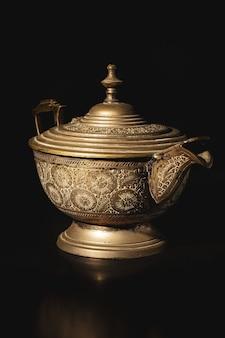 Zilveren metalen oude theepot geïsoleerd op zwart oppervlak