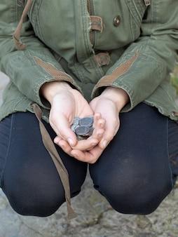 Zilveren munten in handen van de arme zwerver. dakloze vraagt om geld voor eten.